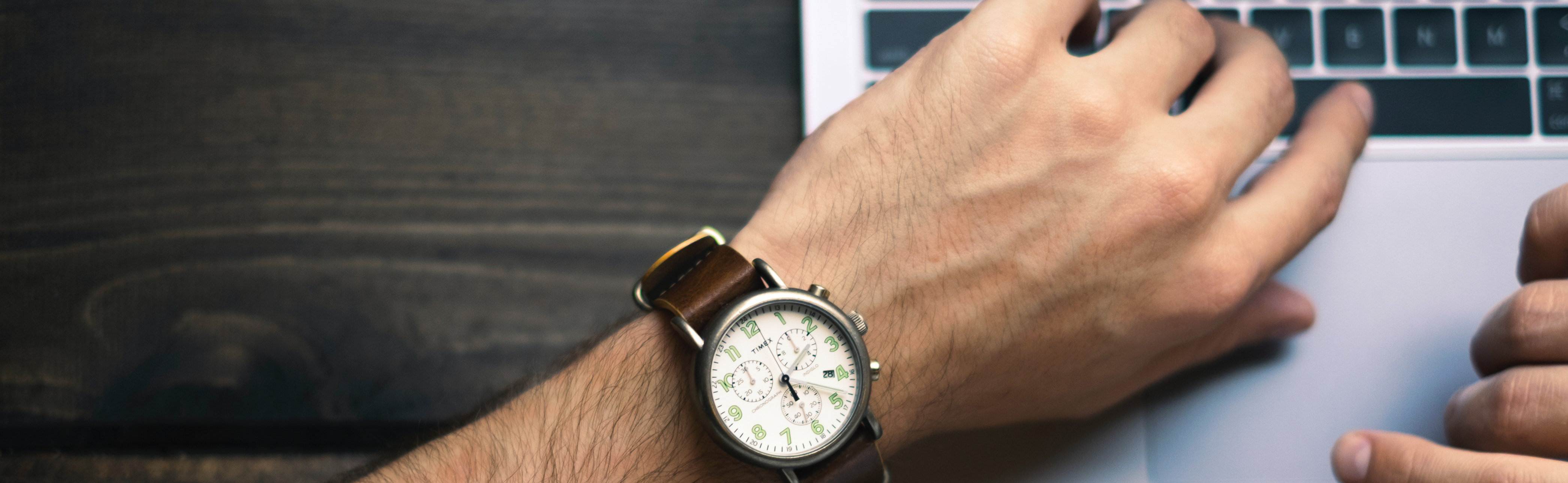 A hand with an analog wrist watch hovering over a laptop keyboard