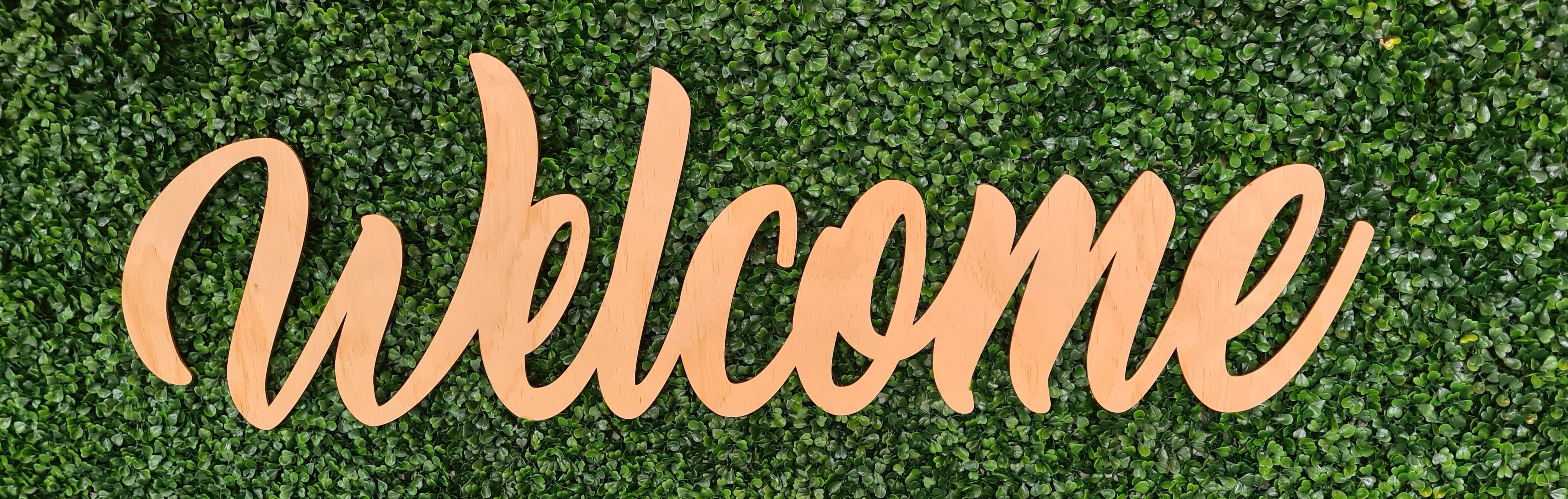 Welcome sign on green grass